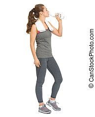Full length portrait of fitness young woman drinking water
