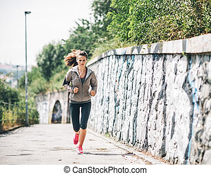Full length portrait of fitness young woman jogging in the city