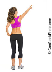 Full length portrait of fitness young woman pointing on copy space . rear view