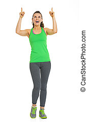 Full length portrait of fitness young woman pointing on copy space