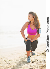 Full length portrait of fitness young woman stretching on beach and looking on copy space