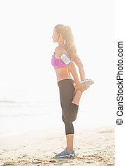 Full length portrait of fitness young woman stretching on beach