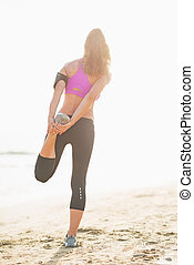Full length portrait of fitness young woman stretching on beach . rear view