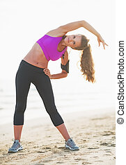 Full length portrait of fitness young woman stretching outdoors