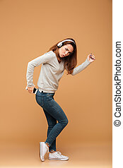 Full length portrait of funny attractive woman in casual wear holding her smartphone while dancing moon walk, looking at camera