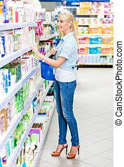 Full length portrait of girl at the shop choosing cosmetics