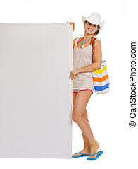 Full length portrait of happy beach young woman showing blank billboard