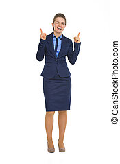 Full length portrait of happy business woman pointing up on copy space