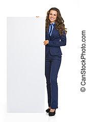 Full length portrait of happy business woman showing blank billboard