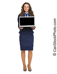 Full length portrait of happy business woman showing laptop blank screen