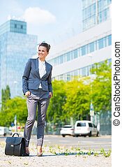 Full length portrait of happy business woman with briefcase in o