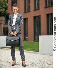 Full length portrait of happy business woman with briefcase