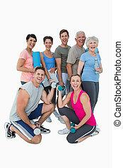 Full length portrait of happy fitness class over white...