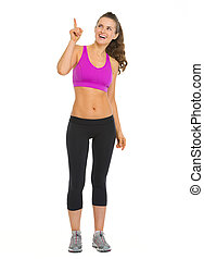 Full length portrait of happy fitness young woman pointing on copy space
