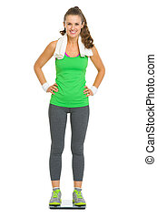 Full length portrait of happy fitness young woman standing on scales