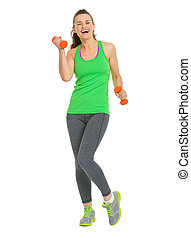 Full length portrait of happy fitness young woman with dumbbells