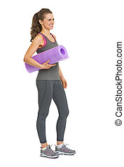 Full length portrait of happy healthy young woman with fitness mat