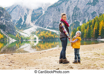 Full length portrait of happy mother and baby on lake braies in