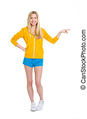 Full length portrait of happy teenager girl pointing on copy space