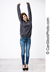 Full length portrait of happy woman with raised hands up