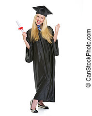 Full length portrait of happy young woman in graduation gown...