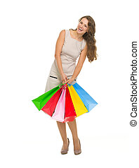 Full length portrait of happy young woman holding shopping bags