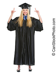 Full length portrait of happy young woman in graduation gown pointing up on copy space