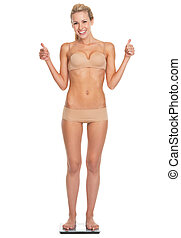 Full length portrait of happy young woman in lingerie standing on scales and showing thumbs up