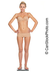 Full length portrait of happy young woman in lingerie standing scales