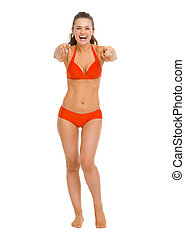 Full length portrait of happy young woman in swimsuit pointing in camera