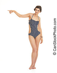 Full length portrait of happy young woman in swimsuit pointing o