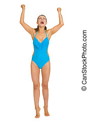 Full length portrait of happy young woman in swimsuit rejoicing
