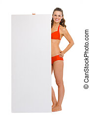 Full length portrait of happy young woman in swimsuit showing blank billboard