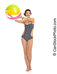 Full length portrait of happy young woman in swimsuit with beach