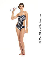 Full length portrait of happy young woman in swimsuit with bottl