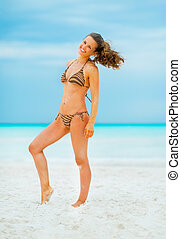 Full length portrait of happy young woman on beach