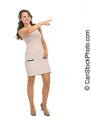 Full length portrait of happy young woman pointing on copy space