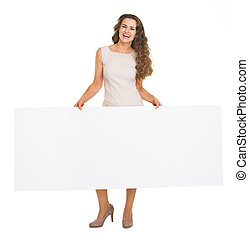Full length portrait of happy young woman showing blank billboard
