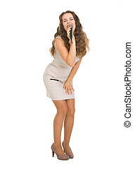 Full length portrait of happy young woman singing with microphone