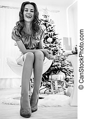 Full length portrait of happy young woman sitting near christmas tree