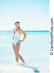 Full length portrait of happy young woman standing at seaside