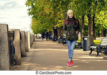 Full length portrait of happy young woman walking with dogs outdoors in autumn
