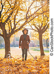 Full length portrait of happy young woman walking with dogs outd