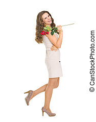 Full length portrait of happy young woman with red rose