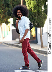 happy youth man with afro walking across street