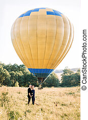 Full length portrait of lovely young couple in black, hugging each other and enjoying summer walk in the field, waiting for their air balloon tour. Yellow air balloon on the background