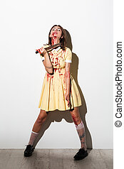 Full length portrait of mad zombie woman bleading