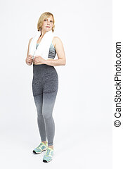 Full Length Portrait of Mature Caucasian Woman In Sportswear Outfit Posing with Towel Over The  Shoulders On White