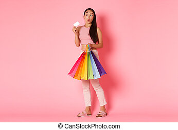 Full length portrait of of excited pretty asian girl in trendy clothes, holding shopping bags and credit, discount card with pleased smile, standing pink background, enjoying weekends in malls