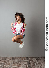 Full-length portrait of pretty jumping girl in casual wear